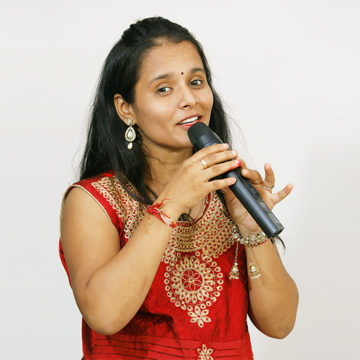 woman with mic in red dress singing